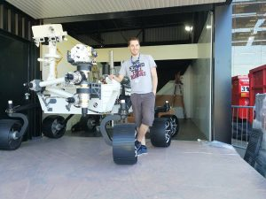 Kevin Costard posant à côté de la maquette du Robot Mars Rover Curiosity